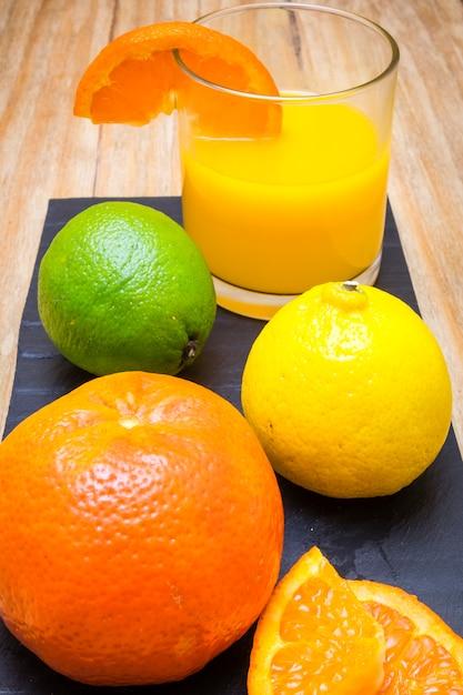 Varios cítricos maduros y un vaso de jugo en una mesa de madera Foto Premium