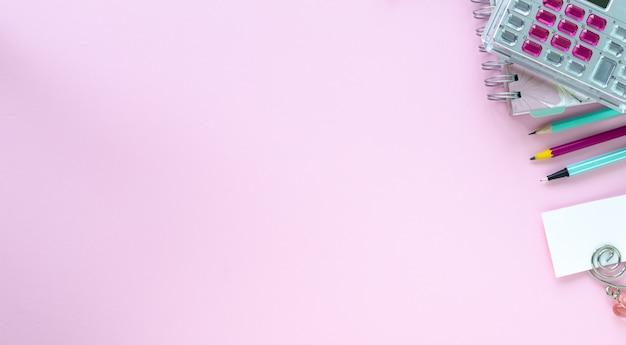 Varios colores de papelería para la escuela y la oficina sobre fondo rosa con copyspace. Foto gratis