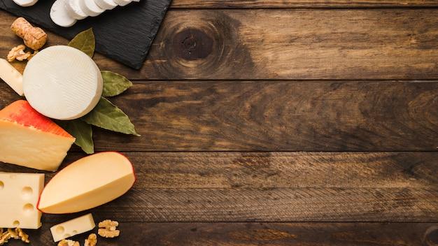 Varios deliciosos quesos con hojas de laurel y nuez en madera con textura Foto gratis