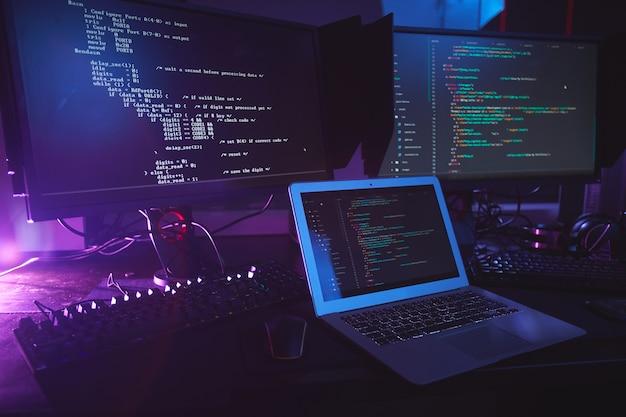 Varios equipos informáticos con código de programación en pantallas en la mesa en una habitación oscura, concepto de seguridad cibernética, espacio de copia Foto Premium
