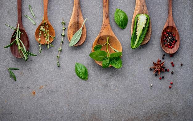 Varios de especias y hierbas en cucharas de madera. Foto Premium