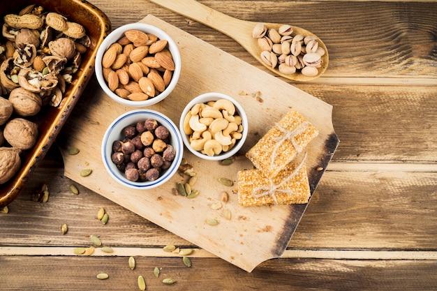 Varios ingredientes saludables y barra de proteína en tabla de cortar Foto gratis