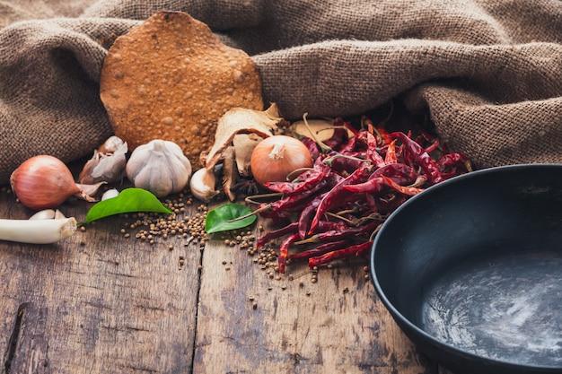 Varios ingredientes utilizados para hacer comida asiática se colocan al lado de la sartén en la mesa de madera. Foto gratis