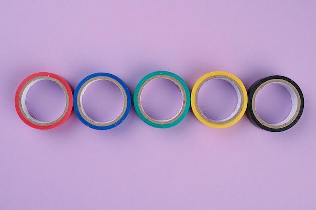 Varios rollos redondos de cinta plástica de colores se encuentran en una fila Foto Premium