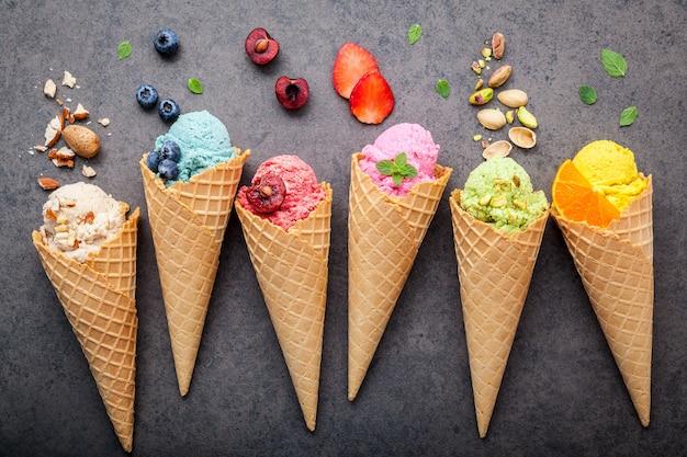 Varios de sabor a helado en configuración de conos sobre fondo de piedra oscura. Foto Premium
