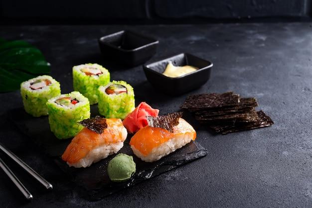 Varios sushi en pizarra negra con palitos de pizarra, salsa y nori en negro Foto Premium