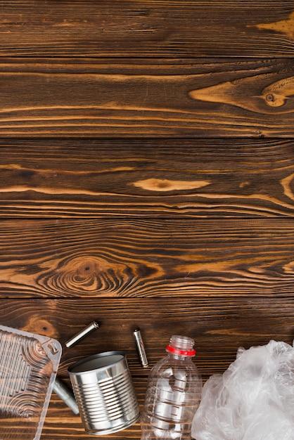 Varios tipos de basura reciclable en el escritorio de madera. Foto gratis