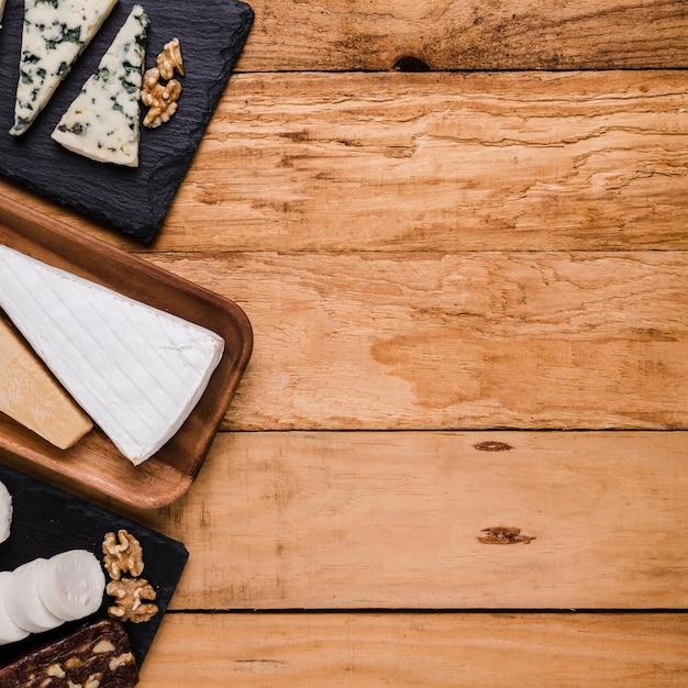 Varios tipos de piezas de queso fresco en placa de madera y bandeja de piedra sobre fondo de madera Foto gratis