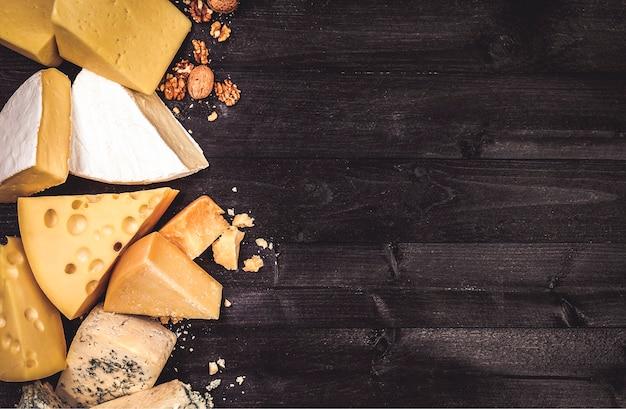 Varios tipos de queso sobre fondo de madera negra con espacio de copia Foto Premium