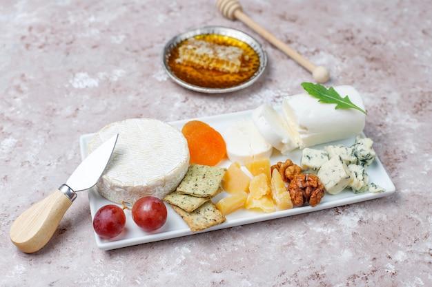 Varios tipos de queso en superficie marrón claro Foto gratis