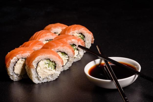 Varios tipos de sushi servido en un oscuro. rodillo con salmón, aguacate, pepino. menú de sushi comida japonesa. Foto Premium