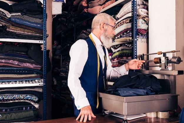 Varón mayor que mide la tela en la máquina en tienda Foto gratis