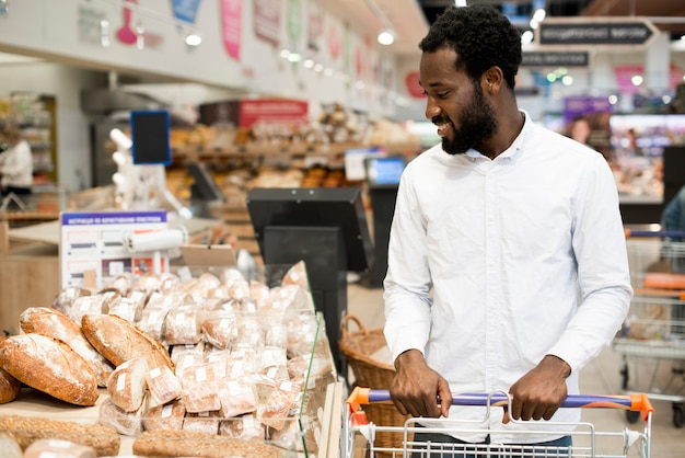 Varón negro feliz que elige el pan en el colmado Foto gratis