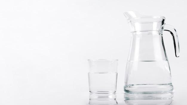 Vaso de agua al lado de jarra Foto gratis