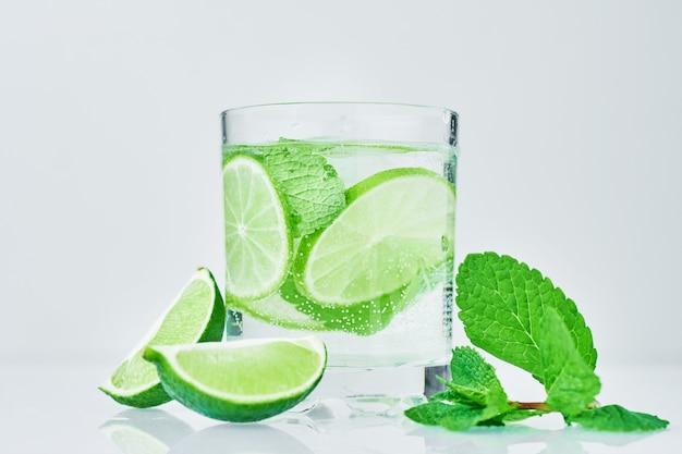 Vaso de agua con limón y menta en blanco Foto Premium