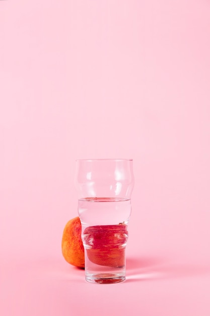 Vaso de agua y nectarina sobre fondo rosa Foto gratis