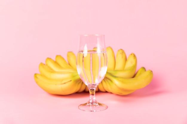 Vaso de agua con plátanos en segundo plano. Foto gratis