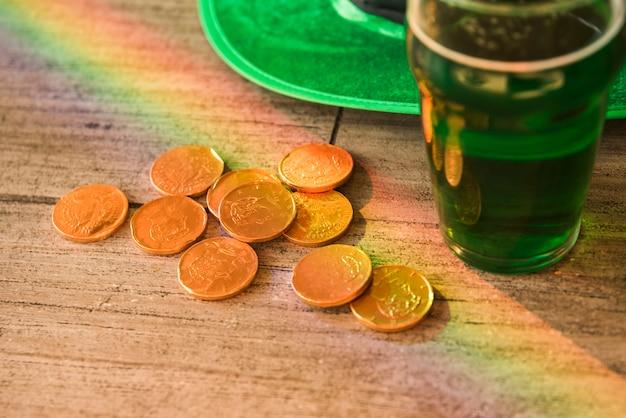 Vaso de bebida cerca del montón de monedas y el sombrero de san patricio en la mesa Foto gratis