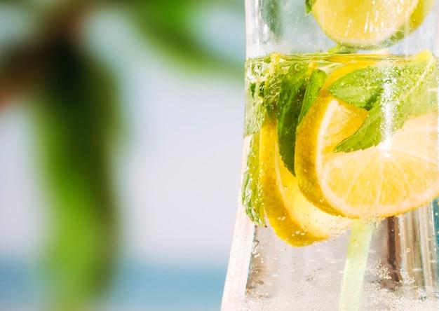 Vaso de bebida fría con rodajas de lima y hojas de menta Foto gratis
