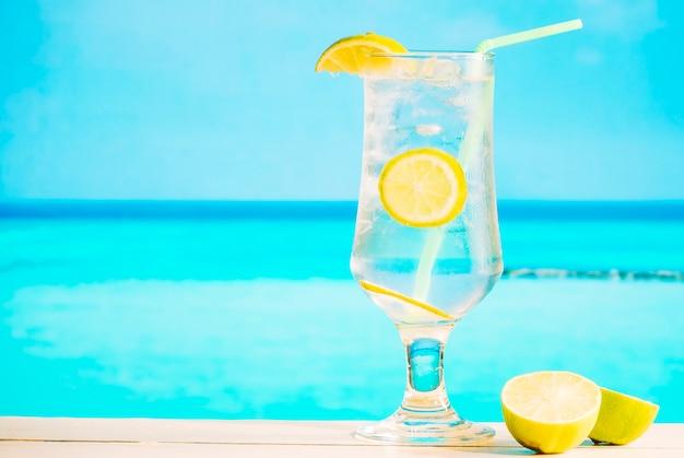 Vaso de bebida de limón fresco con paja y limón en rodajas Foto gratis