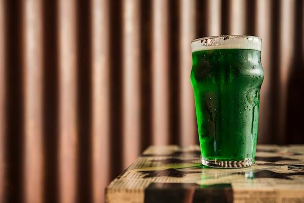 Vaso de bebida verde en la mesa junto a la pared de madera Foto gratis