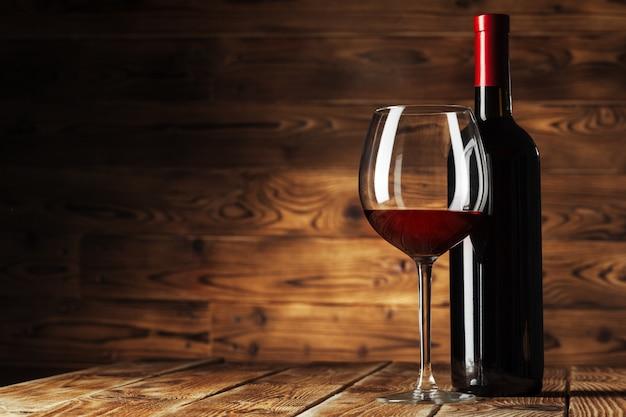 Vaso y botella con delicioso vino tinto en mesa contra madera Foto Premium