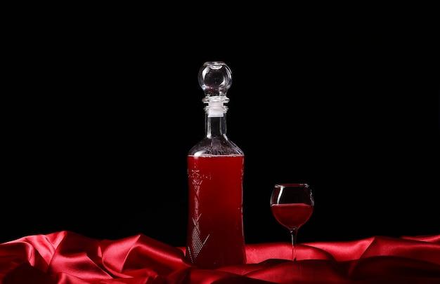 Vaso y botella de vino sobre un fondo oscuro de seda Foto Premium