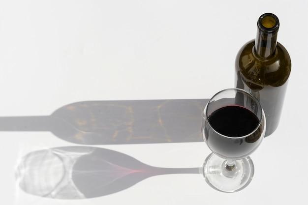 Vaso y botella de vino con sombras oscuras aisladas en blanco Foto Premium