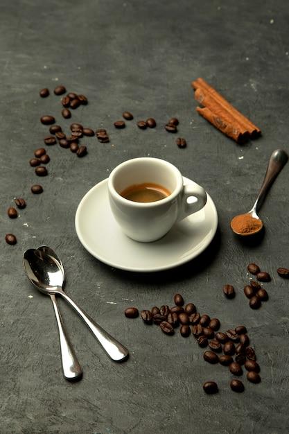 Vaso de café exprés en fondo gris decorado con granos de café. Foto gratis