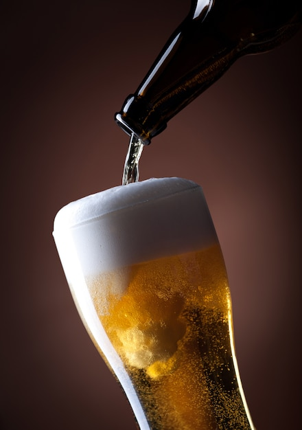 Vaso de cerveza y botella en un marrón Foto Premium
