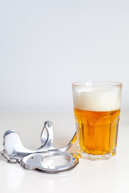 Vaso de cerveza con esposas como símbolo del abuso del alcohol Foto Premium