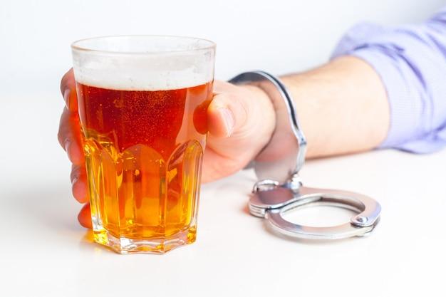 Vaso de cerveza con esposas como símbolo de abuso de alcohol Foto Premium