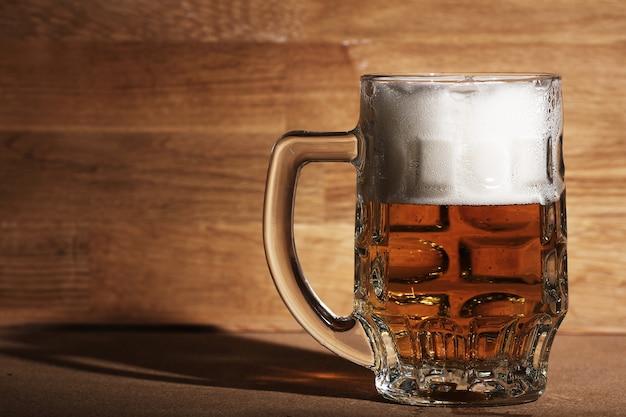 Vaso de cerveza sobre superficie de madera Foto gratis