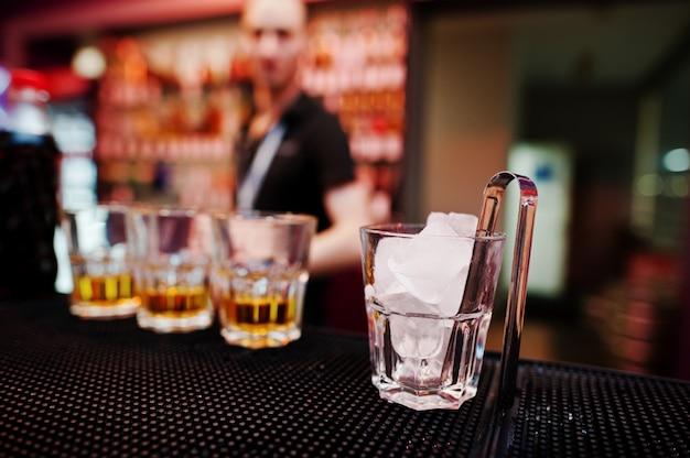 Vaso con hielo y pinzas con tres vasos de whisky de fondo barman Foto Premium