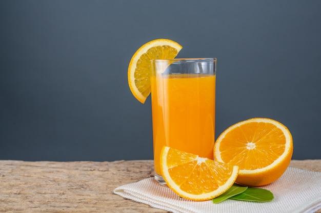 Vaso de jugo de naranja colocado en la madera. Foto gratis