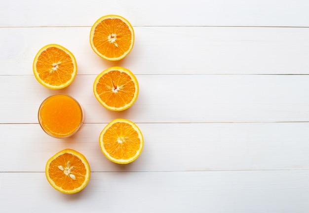 Vaso de jugo de naranja fresco con frutas frescas sobre fondo blanco de madera. Foto Premium