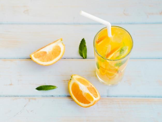 Vaso de jugo de naranja helado con rodajas y paja Foto gratis
