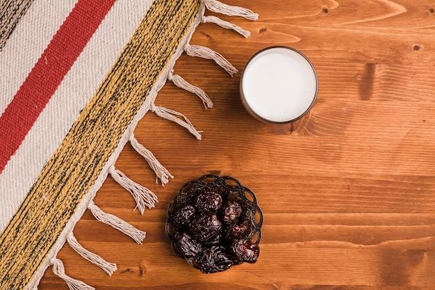 Vaso de leche cerca de platillo con ciruelas dulces y tapete Foto gratis
