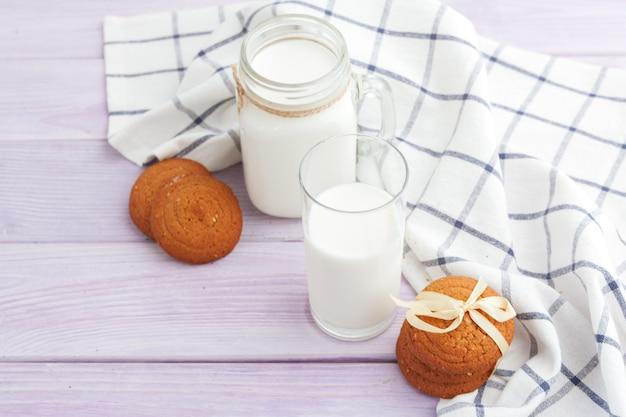 Vaso de leche y galletas con paño de cocina sobre fondo claro Foto Premium