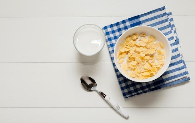 Vaso de leche junto al tazón de cereales sobre tela Foto gratis