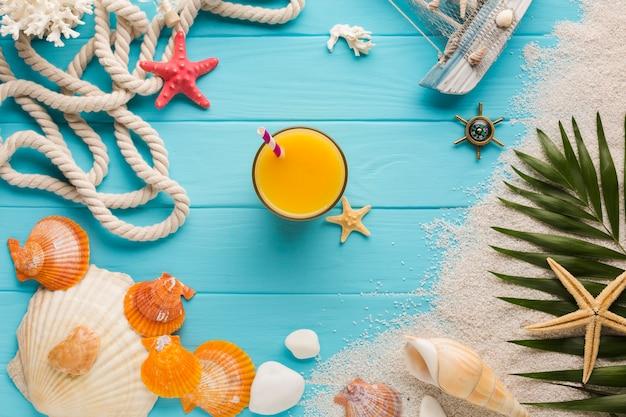 Vaso plano de zumo rodeado de elementos de playa. Foto gratis