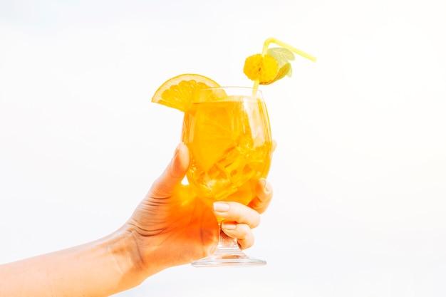 Vaso de refrescante bebida de naranja en la mano Foto gratis