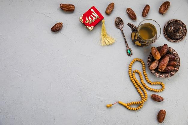 Vaso de té con dátiles frutales y cuentas sobre tabla. Foto gratis