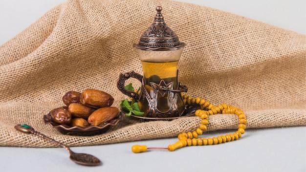Vaso de té con dátiles frutales y rosario. Foto gratis