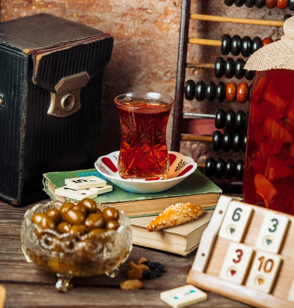 Un vaso de té negro y fechas frescas en una mesa de juego en la tarde. Foto gratis