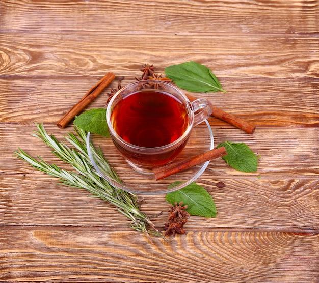 Vaso de té verde con palitos de canela en una pared de mesa de madera. Foto Premium