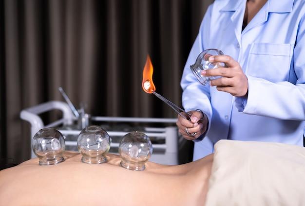 Vaso de vidrio con fuego para tratamiento de ventosas en espalda femenina Foto Premium