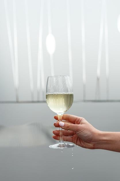 Un vaso de vino blanco en la mano de una mujer. Foto Premium