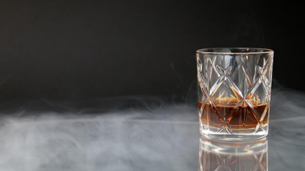 Vaso de whisky en una mesa rodeada de humo sobre un fondo negro Foto gratis