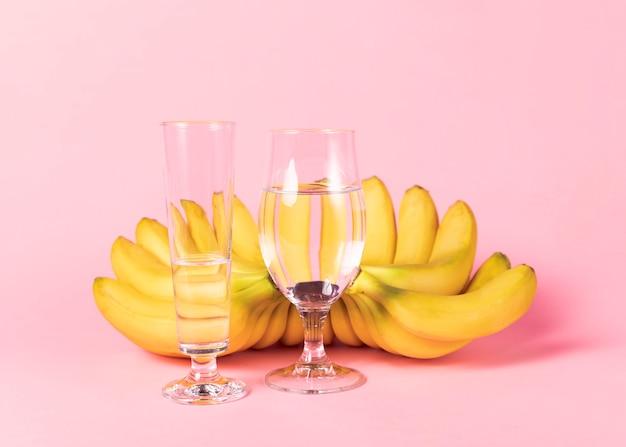 Vasos de agua y racimos de plátanos Foto gratis